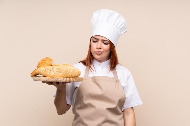 Redhead tienervrouw in eenvormige chef-kok. vrouwelijke bakker die een lijst met verscheidene broden met droevige uitdrukking houdt