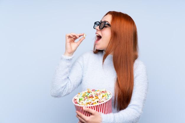 Redhead tienervrouw met 3d glazen en holding een grote emmer popcorns