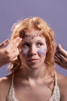 Redhead vrouw bedekt met verf en woorden als een teken van triomf