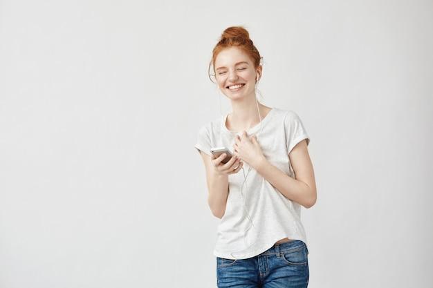 Redhead vrouw luisteren muziek in koptelefoon lachen.