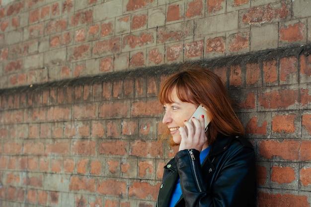 Redhead vrouwvrouw die op haar mobiele telefoon spreekt.