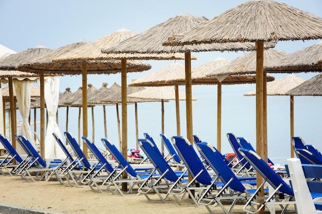 Reed-parasols en ligstoelen bij het strand