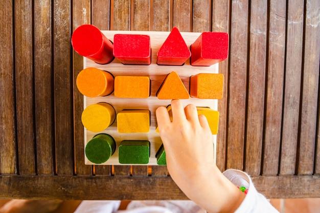 Reeks blokken hout van opeenvolgingen van geometrische die vormen met natuurlijke kleurstoffen worden geschilderd