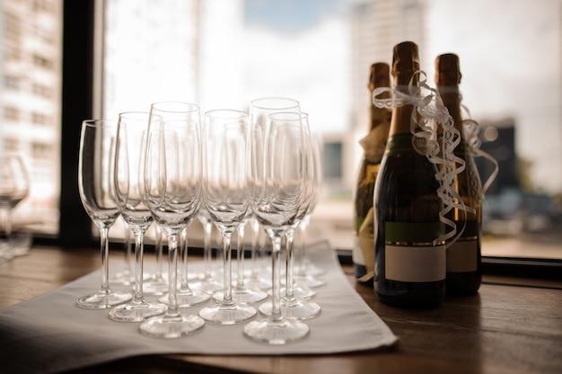 Reeks champagneflessen en lege wijnglazen op het servet