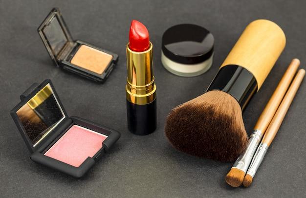 Reeks decoratieve schoonheidsmiddelen en professionele make-uphulpmiddelenborstels op zwarte achtergrond