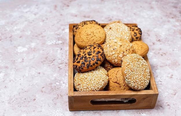 Reeks diverse amerikaanse stijlkoekjes in houten dienblad op lichte concrete achtergrond. zandkoek met sesamzaad, pindakaas, havermout en chocoladeschilferkoekjes.