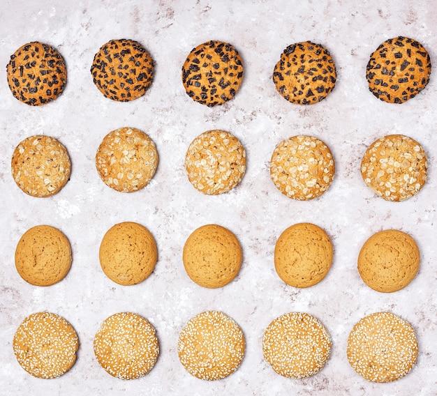 Reeks diverse amerikaanse stijlkoekjes op een lichte concrete achtergrond. zandkoek met confetti, sesamzaad, pindakaas, havermout en chocoladeschilferkoekjes.