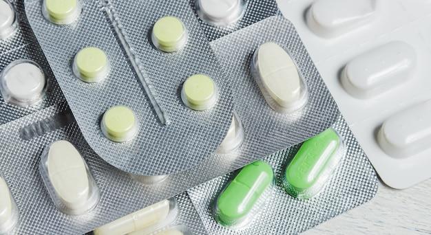 Reeks diverse tabletten en capsules in blaren op witte houten. geneeskunde concept.