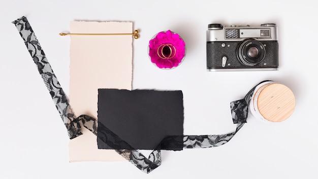 Reeks documenten dichtbij verse bloem met ringen op plaat, retro camera en band