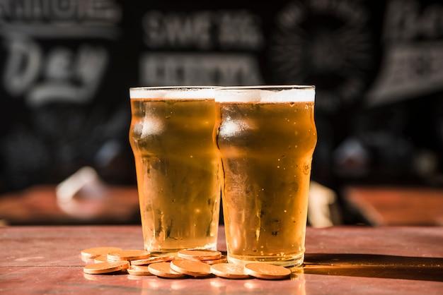 Reeks glazen drank dichtbij hoop van muntstukken bij lijst