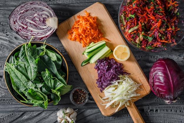 Reeks greens en groentesalade in kommen op een picknickdoek en donkere houten achtergrond. bovenaanzicht. ruimte voor tekst