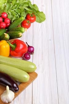 Reeks groenten op een lichte houten achtergrond als achtergrond