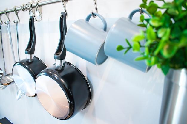Reeks hulpmiddelen die van keukentoebehoren op de muur hangen.