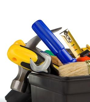 Reeks hulpmiddelen en instrumenten in zwarte plastic doos die op witte achtergrond wordt geïsoleerd