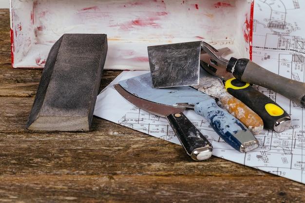Reeks hulpmiddelen en spatel van de pleistertroffel op oud hout als achtergrond.