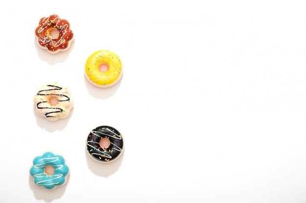 Reeks kleurrijke die donuts op witte achtergrond wordt geïsoleerd.