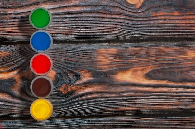 Reeks kleurrijke kruiken van de vingerverf op een rustieke achtergrond