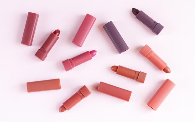 Reeks kleurrijke lippenstiften op lichtroze achtergrond. platliggend, bovenaanzicht