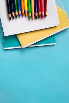 Reeks oefenboeken en kleurpotloden op blauw met ruimte voor tekst.