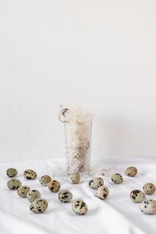 Reeks pasen-kwartelseieren dichtbij hoop van veren in vaas op textiel