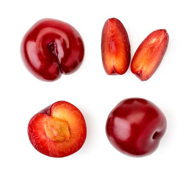 Reeks rode halve pruimen en stukken op wit