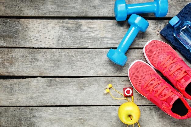 Reeks sporttoebehoren voor fitness met oefeningsapparatuur op grijze houten.
