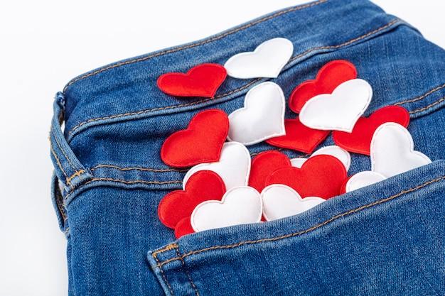 Reeks stoffen rode en witte harten in jeanszak op witte achtergrond.