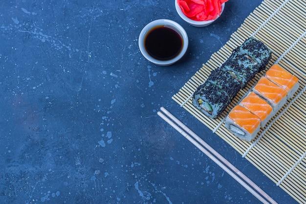 Reeks sushibroodjes met zalm en met omelet, tofu en groenten, vliegende vissenkuiten, tempura op makisu op een donkere lijst. traditioneel japans eten. kopieer ruimte. bovenaanzicht, platliggend