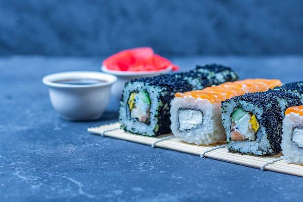 Reeks sushibroodjes met zalm en met omelet, tofu en groenten, vliegende vissenkuiten, tempura op makisu op een donkere lijst. traditioneel japans eten.