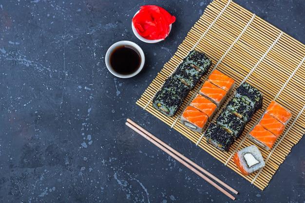 Reeks sushibroodjes met zalm en met omelet, tofu en groenten, vliegende vissenkuiten, tempura op makisu. traditioneel japans eten. detailopname,