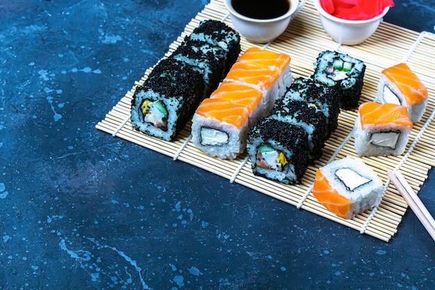 Reeks sushibroodjes met zalm en met omelet, tofu en groenten, vliegende vissenkuiten, tempura op makisu. traditioneel japans eten.