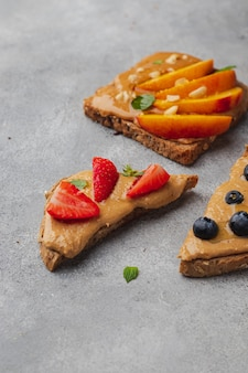 Reeks van diverse toost met pindakaas; honing; munt; pinda, nectarine, bosbes en aardbei
