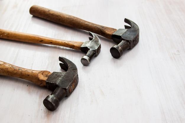 Reeks van hulpmiddel van het drie het uitstekende oude hamerhandvat op de houten witte achtergrond van de verfkleur