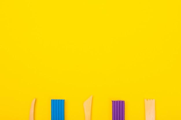 Reeks van kleurrijke plasticine die op gele achtergrond wordt geïsoleerd
