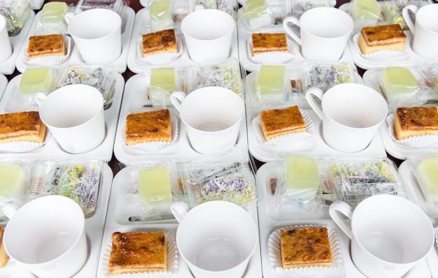 Reeks van kop en snack op schotel voor koffiepauze tussen vergadering met lichte achtergrond