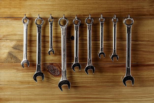 Reeks van moersleutel het hangen bij oude houten muur. industriële werkplaats handgereedschap.
