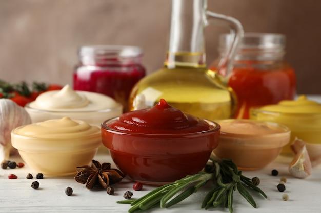 Reeks verschillende heerlijke sauzen, olijfolie, knoflook, tomatenkers op witte lijst tegen bruine achtergrond, close-up