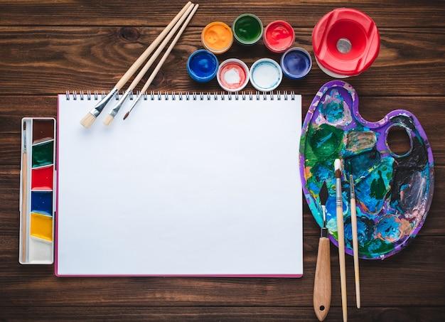 Reeks verven, potloden, hulpmiddelen om te schilderen en leeg witboekblad
