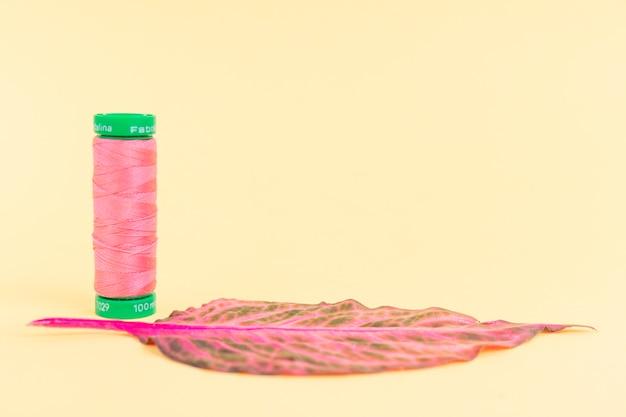 Reel van roze garen met een blad