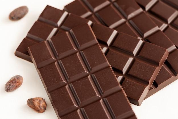 Reep chocolade en cacaobonen op een witte achtergrond.