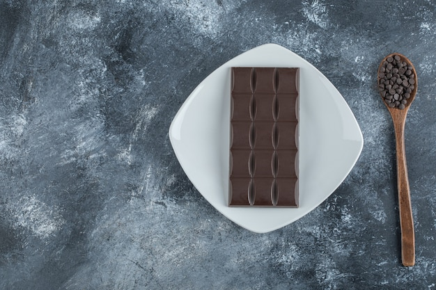 Reep chocolade met chocoladeschilfers op een marmeren oppervlak.