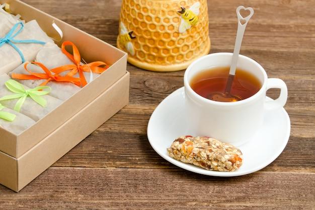 Reep muesli, een mok thee en dozen met repen. gezond ontbijt