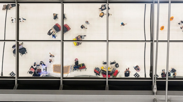 Reflectie glas van bovenaanzicht mensen lopen en zitten in de bank met bagage en koffer om te reizen op de luchthaven