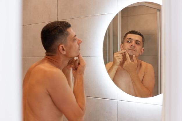 Reflectie in de spiegel knappe donkerharige man staande met naakt bovenlichaam en kijkend naar zijn gezicht, vindt puistje, huidproblemen, ochtendhygiëne procedures.