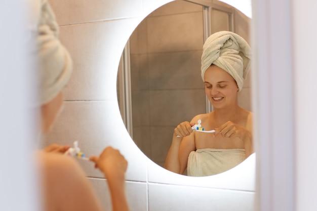 Reflectie in de spiegel van een gelukkige positieve jonge vrouw gewikkeld in een handdoek na het douchen, tandpasta op tanden zetten, mondhygiëne, ochtendroutine.