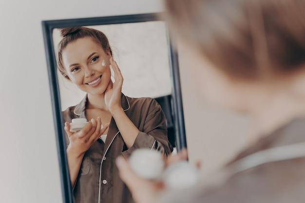 Reflectie in de spiegel van een mooie vrouw in een zijden pyjama die lacht terwijl ze gezichtscrème aanbrengt voor dieper herstel en de gezichtshuid beschermt. huidverzorging, schoonheid en effectief anti-rimpelbehandelingsconcept