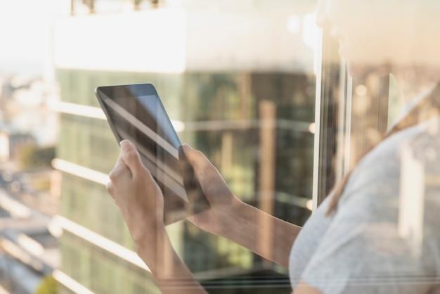 Reflectie op venster van persoon die tablet gebruikt