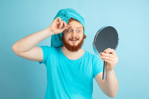 Reflectie. portret van een jonge blanke man in zijn schoonheidsdag en huidverzorgingsroutine. mannelijk model met rood haar dat zijn wenkbrauw vormt die spiegel gebruikt. lichaams- en gezichtsverzorging, natuurlijk, mannelijk schoonheidsconcept.