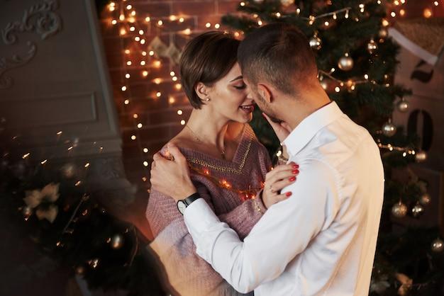 Reflectie van de kerstboom. de nabijheid van de man en het meisje in luxe draagt dat dansen en flirten