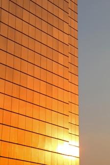 Reflectie van de zon in de gevel van een wolkenkrabber
